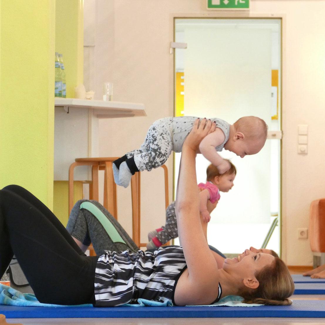Eine Mutter turnt mit Ihrem Baby bei Mama & Baby AKTIV in der Elternschule Pforzheim