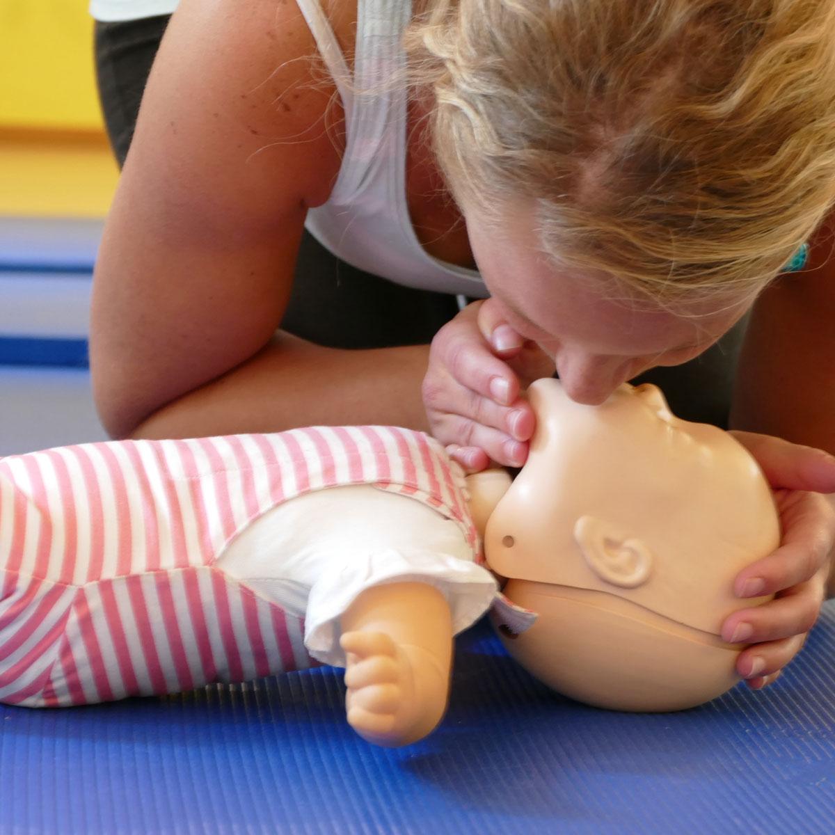 Die Kursleiterin zeigt die Wiederbelebung an einer Puppe im Kurs Erste Hilfe bei Kindernotfällen.